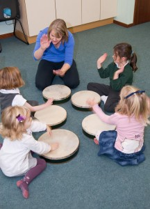 Ali playing drums with here Kindermusik After School Classes in Haslemere